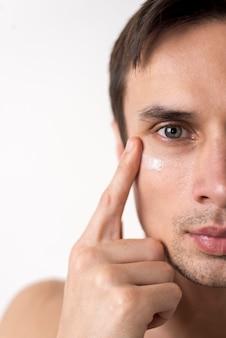 Chiuda sul ritratto dell'uomo che applica la crema per il viso
