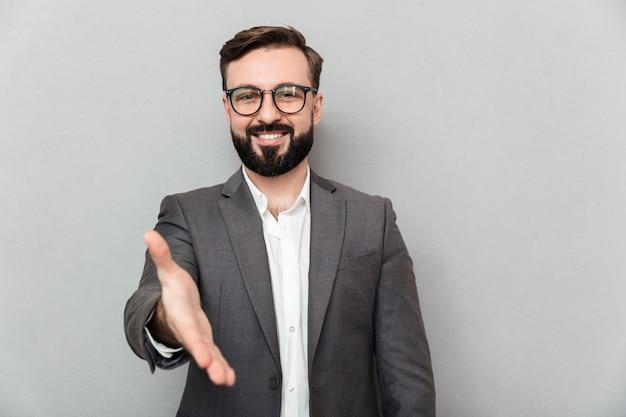 Chiuda sul ritratto dell'uomo gentile amichevole in occhiali che osservano sulla macchina fotografica con il sorriso sincero, offrendo la stretta di mano isolata sopra grey