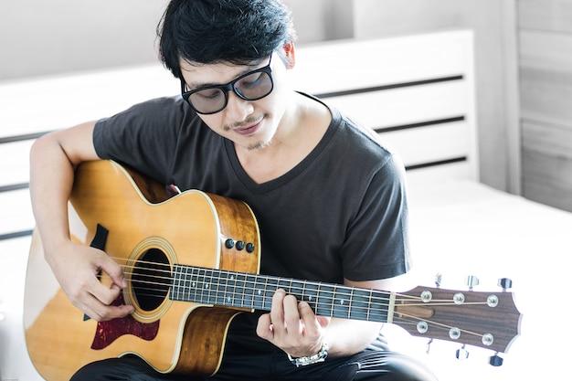 Chiuda sul ritratto dell'uomo in occhiali che gioca la chitarra acustica