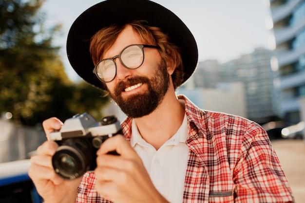 Chiuda sul ritratto dell'uomo sorridente della barba dei pantaloni a vita bassa che usando la retro macchina da presa