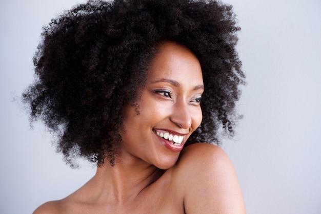 Chiuda sul ritratto della donna africana con sorridere nudo delle spalle