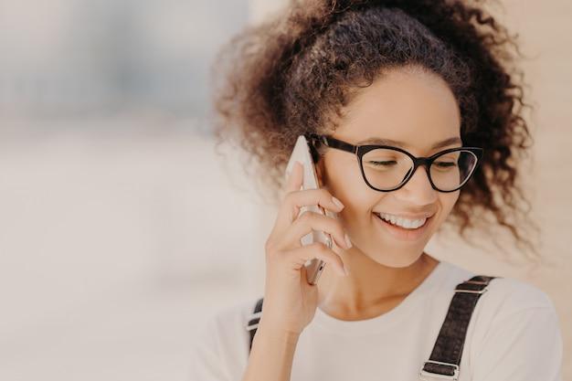 Chiuda sul ritratto della donna allegra con capelli croccanti, soddisfatto delle tariffe per la telefonata