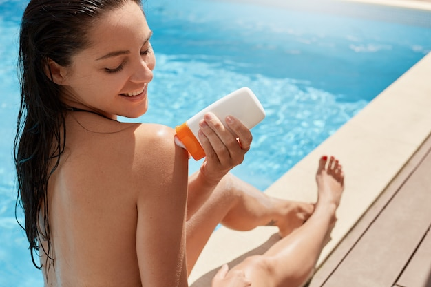 Chiuda sul ritratto della donna allegra felice che si siede sotto i raggi del sole, prendendo il sole con piacere, applicando la crema prendente il sole per proteggere la pelle, trascorrendo il tempo vicino alla piscina all'aperto. concetto di cura della pelle.