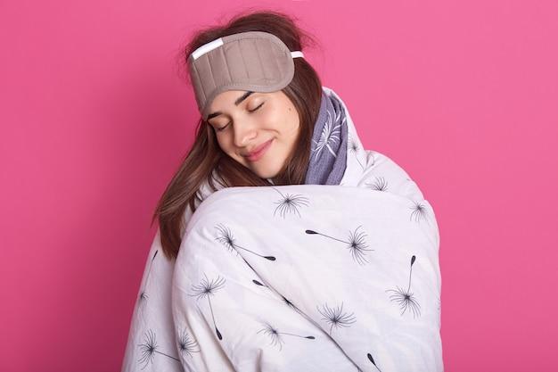 Chiuda sul ritratto della donna attraente con la maschera di sonno sulla testa e sulla coperta d'uso