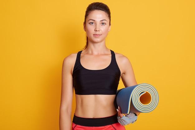 Chiuda sul ritratto della donna di forma fisica pronta per l'allenamento, la ragazza esile che sta contro la parete gialla dello studio e che tiene la stuoia di yoga