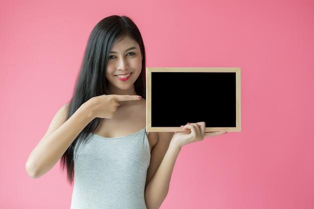 Chiuda sul ritratto della donna di risata positiva che sorride e che tiene il manifesto su fondo rosa