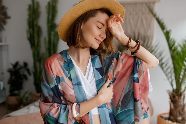 Chiuda sul ritratto della donna elegante in cappello di paglia che posa nella sua camera da letto nello stile di boho