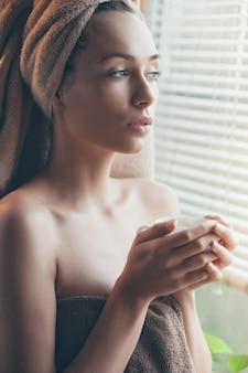 Chiuda sul ritratto della donna graziosa che beve il caffè in accappatoio