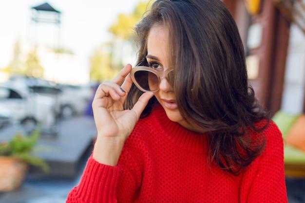 Chiuda sul ritratto della donna romantica elegante con i capelli ondulati del brunette con i retro occhiali da sole alla moda e il maglione lavorato a maglia mer la femmina che si raffredda in caffè moderno di mattina e beve il caffè.