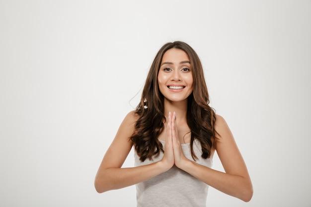 Chiuda sul ritratto della donna soddisfatta, sorridendo e tenendo insieme le palme per pregare isolato sopra bianco