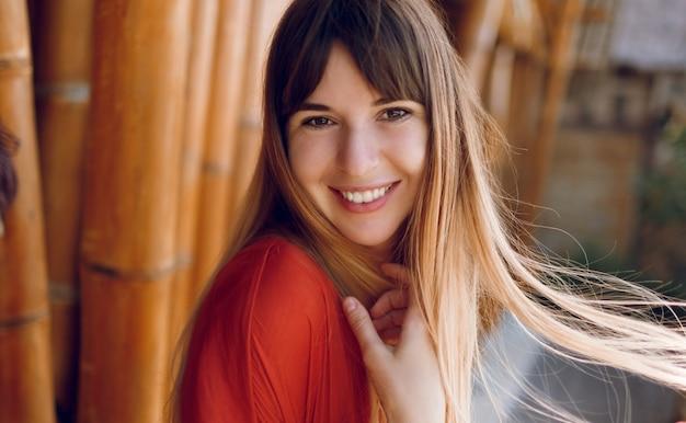 Chiuda sul ritratto della donna sorridente con il sorriso schietto bianco