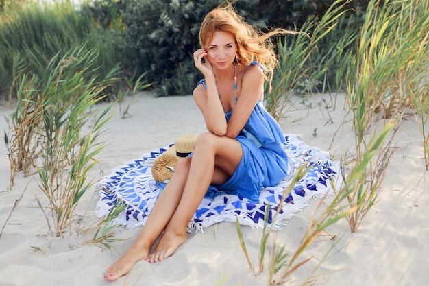 Chiuda sul ritratto della donna sorridente stupefacente della testarossa in vestito blu che si rilassa sulla spiaggia soleggiata di primavera sul tovagliolo. cappello di paglia, eleganti bracciali e collana.