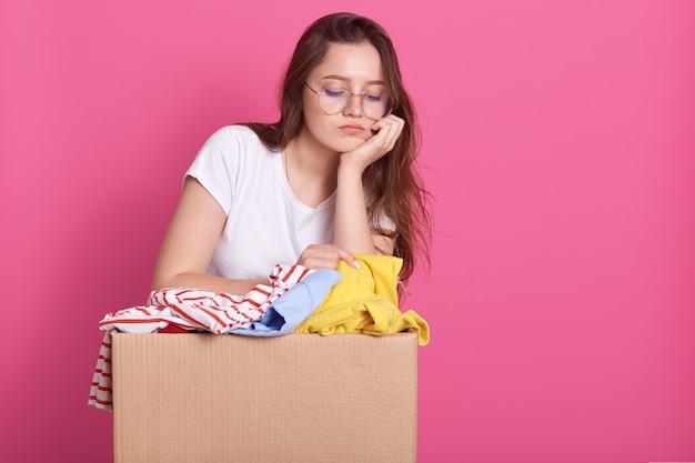 Chiuda sul ritratto della giovane donna infelice che posa con la scatola di donazione dei vestiti, ha espressione facciale triste