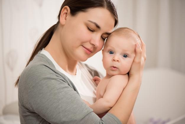 Chiuda sul ritratto della madre e del suo bambino appena nato. concetto di festa della mamma di stile di vita della donna di amore medico e sanitario.