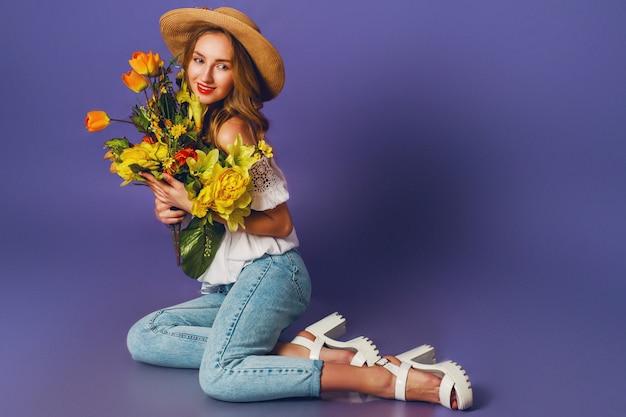 Chiuda sul ritratto della molla di bella giovane signora bionda in cappello alla moda dell'estate della paglia che tiene il mazzo variopinto del fiore della molla vicino al fondo porpora della parete.