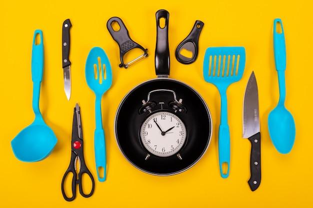 Chiuda sul ritratto della padella con l'insieme degli utensili della cucina su fondo giallo