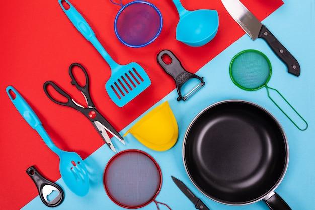 Chiuda sul ritratto della padella con l'insieme degli utensili della cucina