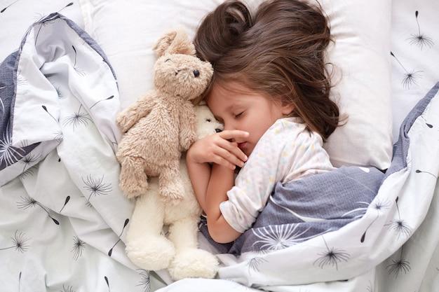 Chiuda sul ritratto della ragazza del bambino che pone con il suo orsacchiotto del giocattolo a letto, che posa con gli occhi chiusi, che ha resto dopo la giornata campale