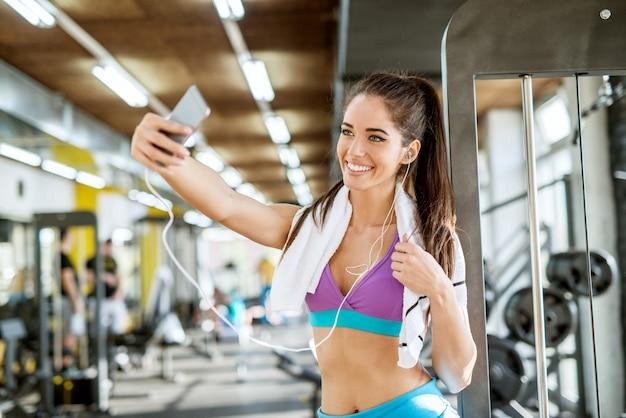 Chiuda sul ritratto della ragazza di forma fitness attiva giovane attraente sorridente felice soddisfatta in piedi con gli auricolari e l'asciugamano e prendendo un selfie in palestra.