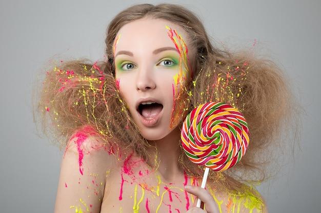 Chiuda sul ritratto della ragazza divertente con il lecca-lecca