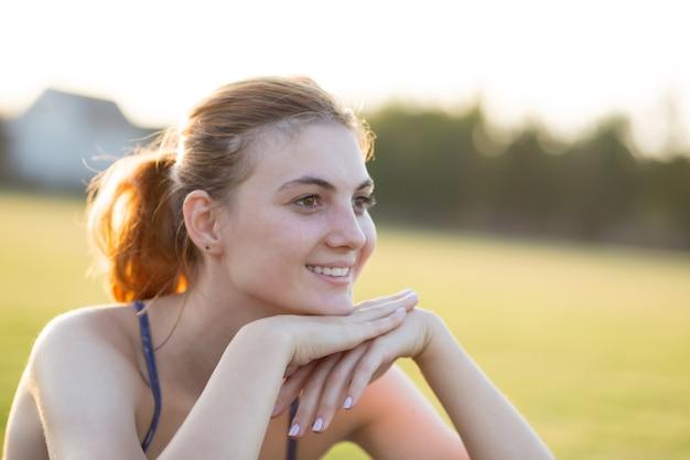 Chiuda sul ritratto della ragazza sorridente allegra con le lentiggini sul suo fronte all'aperto nel giorno di estate soleggiato. concetto di espressioni ed emozioni umane.