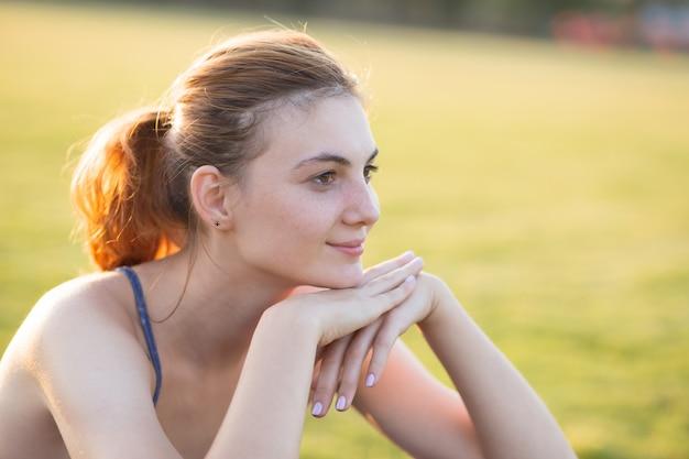 Chiuda sul ritratto della ragazza sorridente allegra con le lentiggini sul suo fronte all'aperto nel giorno di estate soleggiato. espressioni ed emozioni umane.