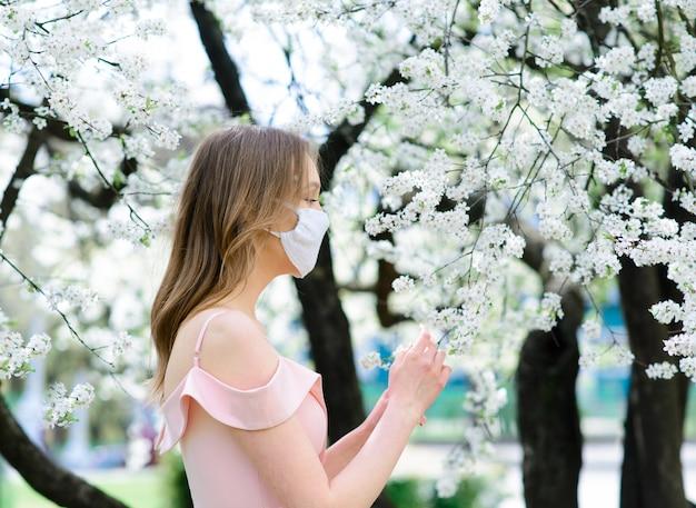 Chiuda sul ritratto della ragazza tenera in una camicetta bianca sotto un ciliegio in fiore con una maschera dal coronavirus.
