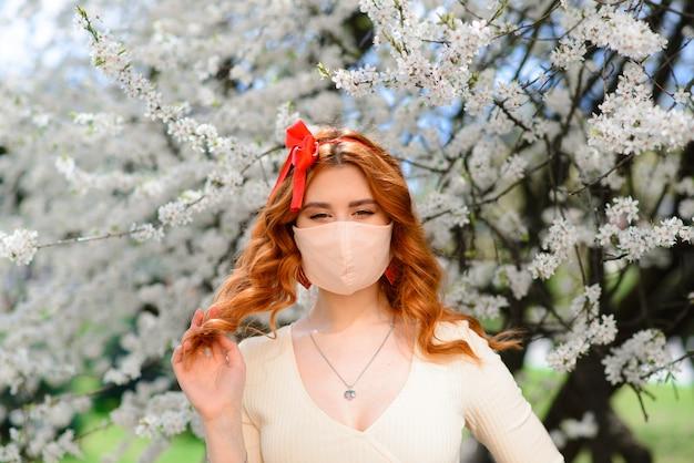Chiuda sul ritratto della ragazza tenera in una camicetta bianca sotto un ciliegio sbocciante con una maschera con i fiori sopra dal coronavirus.