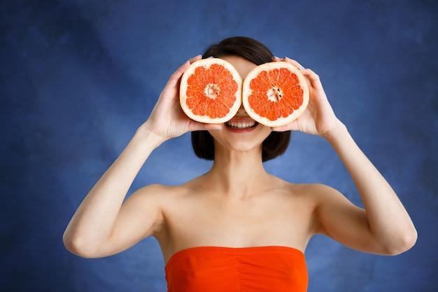 Chiuda sul ritratto della tenuta tenera della giovane donna che ha tagliato l'arancia sopra la parete blu
