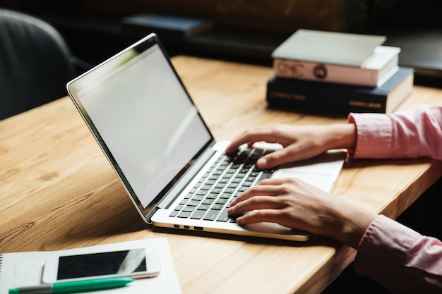 Chiuda sul ritratto delle mani maschii che scrivono sul computer portatile