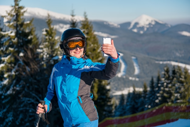 Chiuda sul ritratto dello sciatore della donna che sorride, facendo uso del suo smart phone che prende le foto