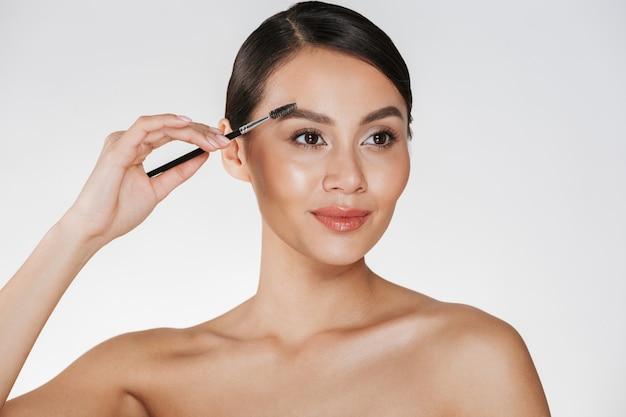 Chiuda sul ritratto dello studio di bella donna castana con pelle molle che dipinge le sue sopracciglia con la spazzola di trucco, isolata sopra bianco