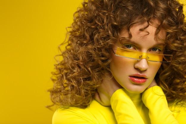 Chiuda sul ritratto dello studio di modo di giovani belle donne con capelli ricci
