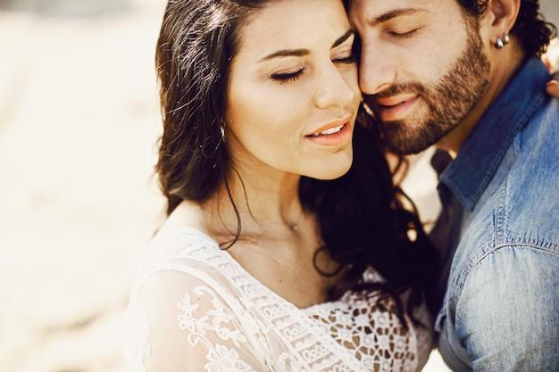 Chiuda sul ritratto di bella coppia di amore alla spiaggia