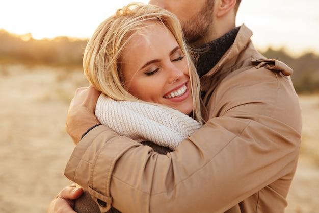 Chiuda sul ritratto di bella coppia nell'amore che abbraccia