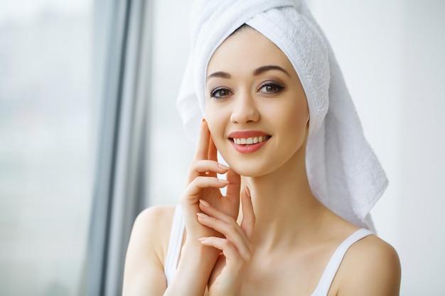 Chiuda sul ritratto di bella donna in asciugamani avvolti intorno alla testa e al corpo, in piedi nel bagno