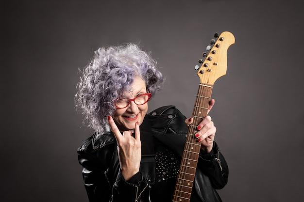 Chiuda sul ritratto di bella donna più anziana che tiene una chitarra elettrica
