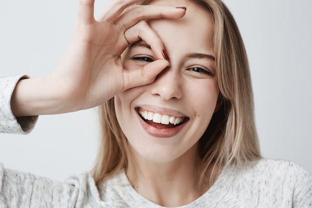Chiuda sul ritratto di bella femmina bionda caucasica allegra che sorride, dimostrando i denti bianchi, guardanti tramite le dita nel gesto giusto. espressioni facciali, emozioni e linguaggio del corpo