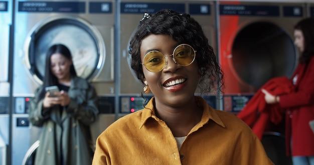 Chiuda sul ritratto di bella giovane donna afroamericana in occhiali da sole gialli che sorridono allegramente alla macchina fotografica nella lavanderia automatica pubblica con le lavatrici