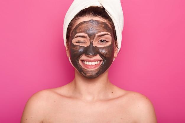 Chiuda sul ritratto di bella giovane donna caucasica che riposa con l'anti maschera di acnee del chocholate nel salone della stazione termale di wellnes, posa mezzo nudo, mostra le spalle nude, sbatte le palpebre con l'occhio. concetto di bellezza e cura della pelle.