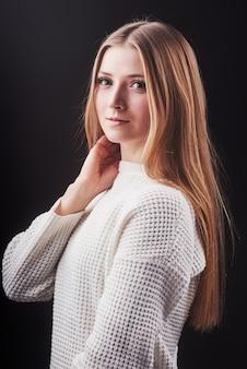 Chiuda sul ritratto di bella giovane donna in maglione bianco e jeans isolati su fondo nero