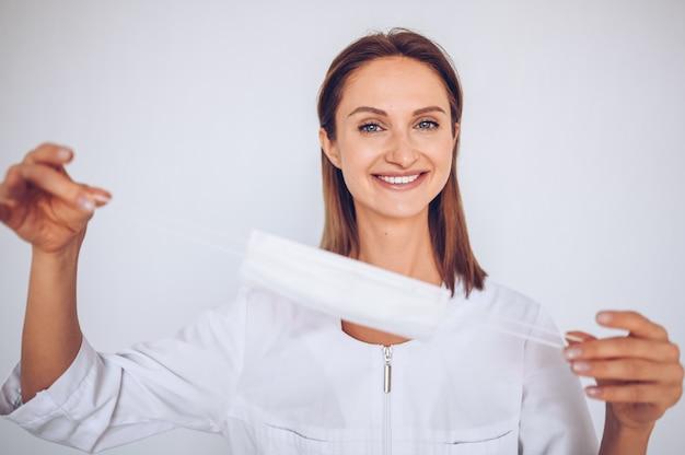 Chiuda sul ritratto di bella giovane infermiera europea del medico della donna che indossa la prevenzione del virus della corona della maschera protettiva. evitare di contaminare il concetto di covid-19 del virus corona