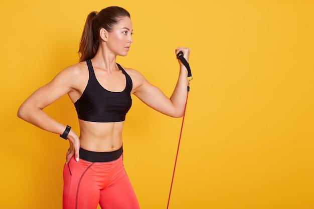 Chiuda sul ritratto di bella ragazza atletica si esercita facendo uso della banda di resistenza, giovane. forza, motivazione e concetto di fitness.