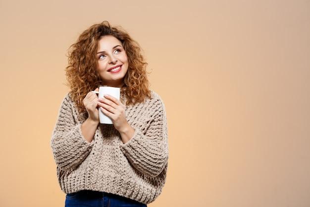 Chiuda sul ritratto di bella ragazza riccia castana sorridente allegra in maglione tricottato che tiene la tazza sopra la parete beige