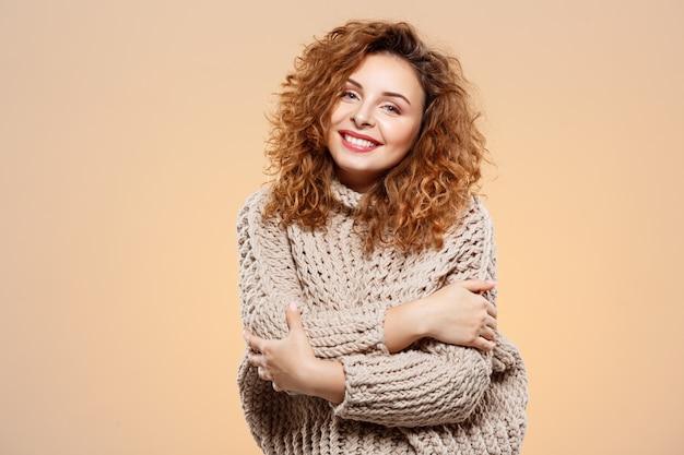 Chiuda sul ritratto di bella ragazza riccia castana sorridente allegra in maglione tricottato sopra la parete beige