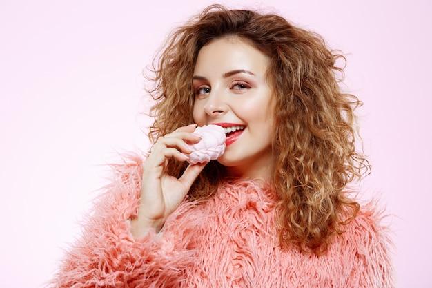 Chiuda sul ritratto di bella ragazza riccia castana sorridente allegra in pelliccia rosa che mangia la caramella gommosa e molle sopra la parete bianca