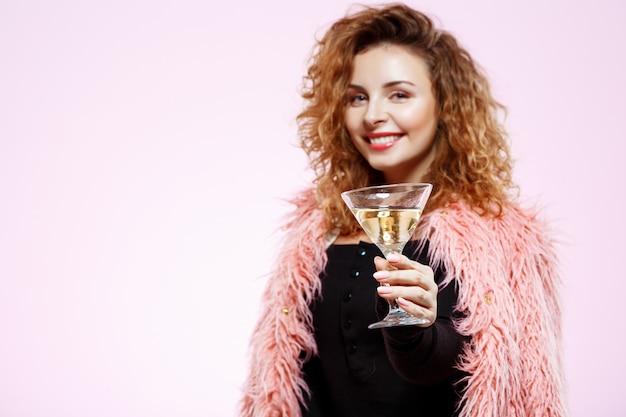 Chiuda sul ritratto di bella ragazza riccia castana sorridente allegra in pelliccia rosa che tiene il vetro di cocktail sopra la parete bianca