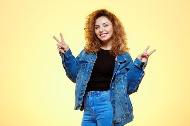 Chiuda sul ritratto di bella ragazza riccia castana sorridente in rivestimento casuale dei jeans della via che mostra il gesto di vittoria sopra la parete gialla