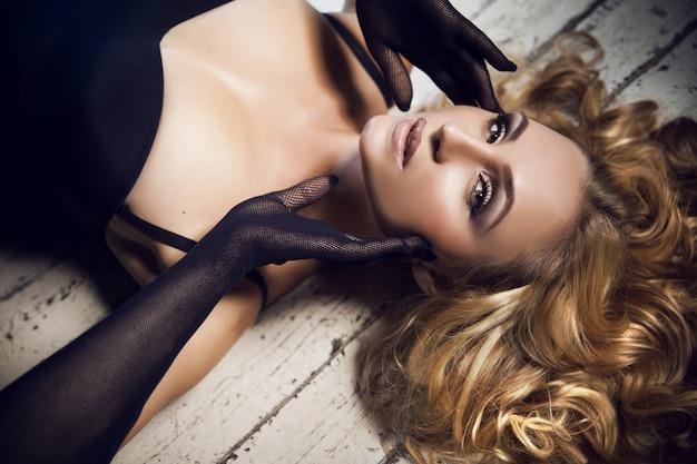Chiuda sul ritratto di bella sensuale giovane e bella signora bionda con la moda trucco e acconciatura riccia in tuta nera e guanti a rete in posa su un pavimento di legno bianco