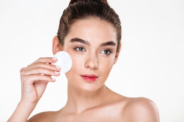 Chiuda sul ritratto di bellezza della donna attraente castana che pulisce il suo fronte con il cuscinetto di cotone